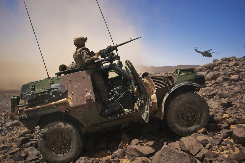 A French soldier stands guard in an armoured vehicle as a helicopter carrying Army Chief of Staff General Bertrand Ract-Madoux leaves a position in the Terz valley