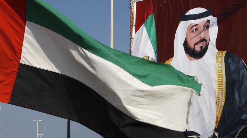 A United Arab Emirates flag waves in front of a big poster of President Sheikh Khalifa bin Zayed al-Nahayan in Abu Dhabi