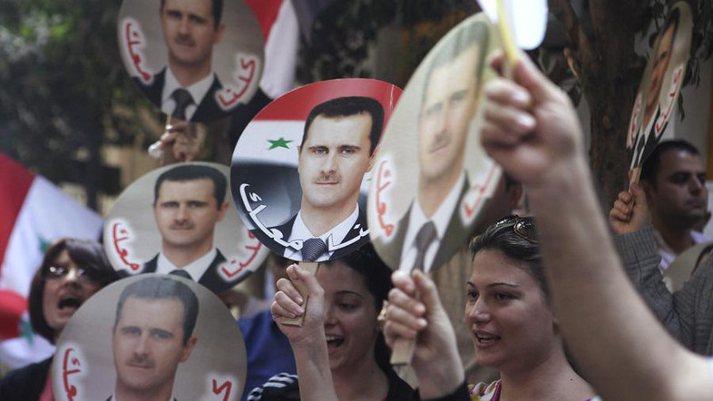 Syrians living in Egypt hold pictures of Syrian President Assad during a pro-Assad rally in front of the Syrian embassy in Cairo